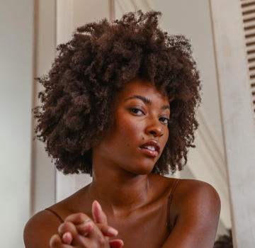 Woman with tightly coiled brown hair